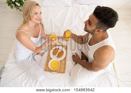 Young Couple Breakfast Sitting In Bed, Happy Smile Young Hispanic Man And Woman Morning Top Angle View Lovers Bedroom