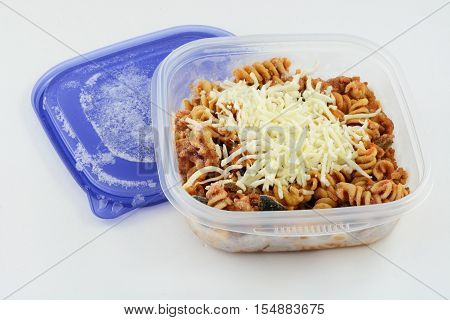 Frozen casserole portion in plastic container on white background