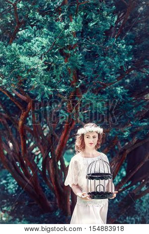 Portrait of beautiful Caucasian young women girl in white dress with flower chaplet holding empty birdcage in enchanted forest alone dreamy romantic gothic style