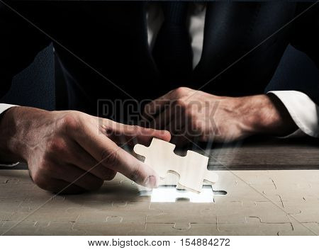 Businessman complete a puzzle inserting last piece