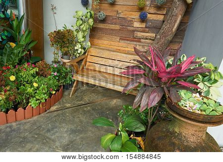 Wooden bench at indoor garden. Wooden bench is decorated with garden tree.