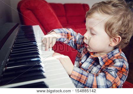 Closeup portrait of cute white Caucasian toddler boy child playing piano indoors with bright sunlight on room lifestyle everyday candid moment