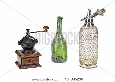 Old coffee mill, green bottle and glass siphon on an isolated studio background