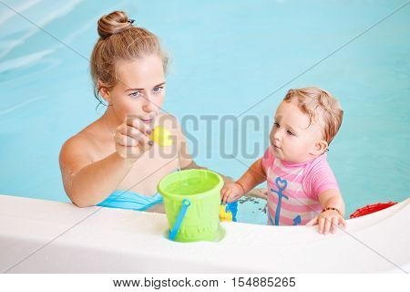 Group portrait of white Caucasian mother and baby daughter playing with toys in water on swimming poo nosing inside training to swim healthy active lifestyle