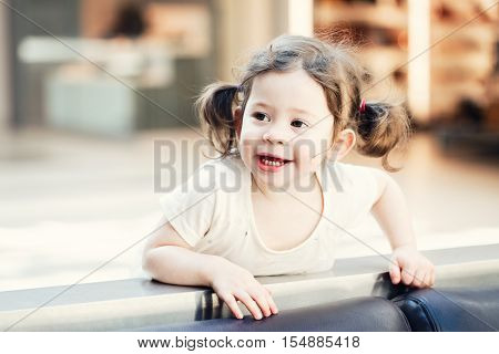 Closeup portrait of cute adorable smiling white Caucasian toddler girl child with dark brown eyes and curly pig-tails hair in white light dress tshirt looking in camera copyspace for text