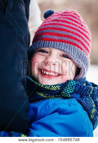 Closeup portrait of smiling laughing Caucasian white toddler boy child in winter clothes hugging his mother parent outside winter fun lifestyle concept beautiful smile natural emotional face expression
