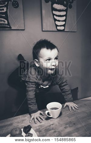 Close-up black and white candid natural portrait of cute adorable little boy toddler in kitchen indoors making funny face lifestyle documentary style grainy film effect poster