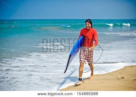 Man In Wetsuit With A Surfboard At The Beach