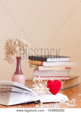 Closeup of open book with withered flowers hydrangea and a small red heart pile of books on the background on wooden table soft focus blurry copyspace for text concept of autumn fall education nostalgic look