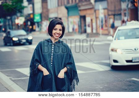 Portrait of beautiful smiling young hipster latin hispanic girl woman with short hair bob in torn jeans grey blue poncho cape standing outside in city street looking in camera street fashion concept