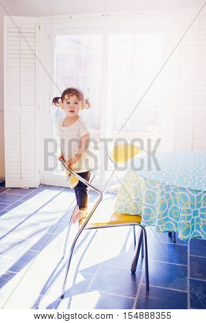 Portrait of adorable toddler girl in white dress with curly hair pig-tails standing on chair in kitchen looking in camera early morning sunlight beams from window touching everyday lifestyle moment