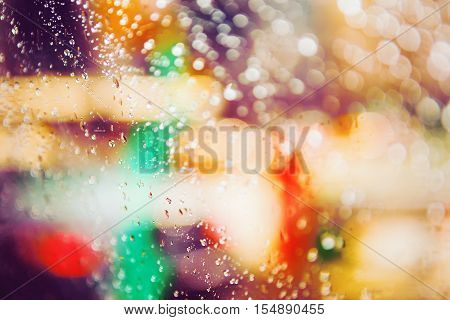 Abstract colorful blurred blurry background warm colors tones cinematic bokeh effect water drops on the window