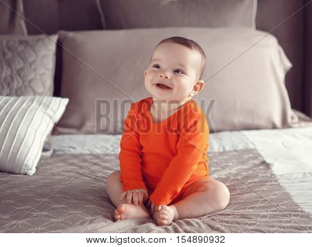 Portrait of cute adorable Caucasian smiling laughing baby boy girl with black brown eyes in orange red onesie shirt sitting on bed lookingaway from camera natural window light lifestyle