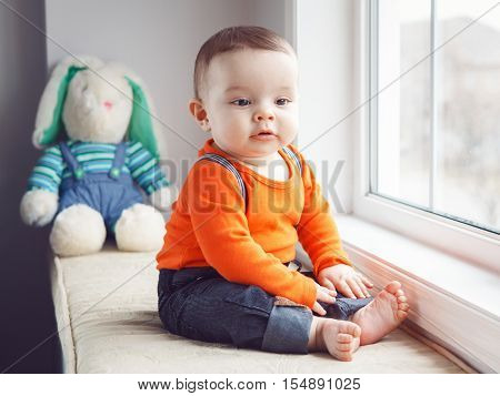 Portrait of cute adorable Caucasian baby boy in orange shirt onesie jeans with suspenders barefoot sitting with bunny toy on windowsill looking away natural window light lifestyle