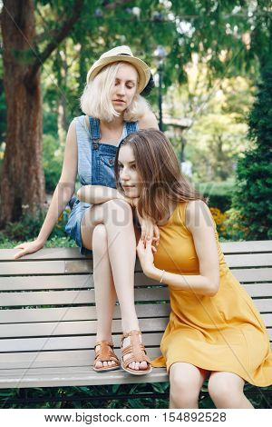 Portrait of two white Caucasian unformal young girls hipster students teenagers friends outside in park on summer day sitting on bench together best friends forever