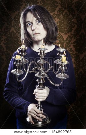 Old crazy woman holding a dusty and tarnished candelabra