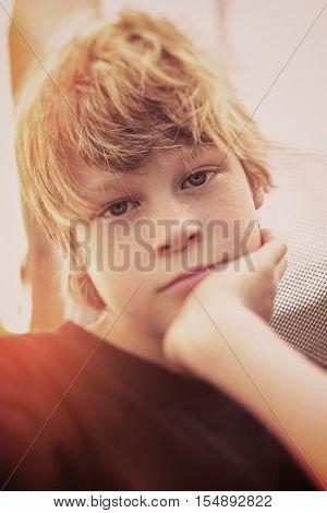 Serious boy, shallow tilt shift, focus on right eye