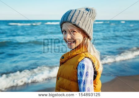 Portrait of smiling blonde white Caucasian child kid girl with long hair wearing yellow jacket gilet and grey hat on beach at sunset looking in camera autumn fall happy lifestyle childhood