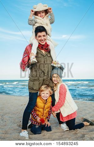 Group portrait of white Caucasian family mother with three children kids hugging smiling laughing on ocean sea beach on sunset outdoors looking in camera happy lifestyle childhood concept