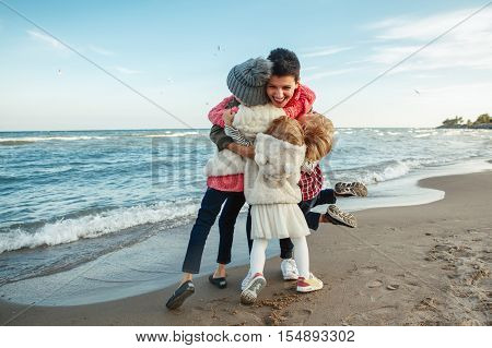Group portrait of white Caucasian family mother with three children kids hugging smiling laughing on ocean sea beach on sunset outdoors happy lifestyle childhood concept