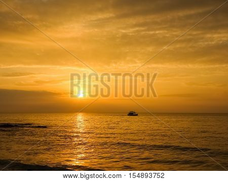Scenic view of beautiful sunset above the sea and silhouette a boat