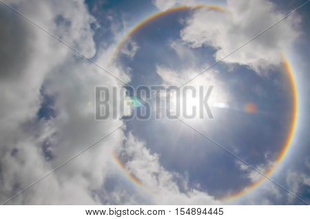 Sun with circular rainbow sun halo occurring due to ice crystals in atmosphere in thai