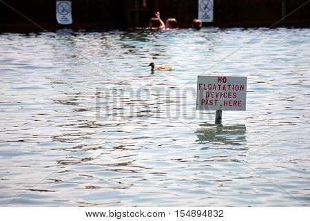 HARBOR SPRINGS, MICHIGAN / UNITED STATES - AUGUST 3, 2016: A sign indicates the limit where swimmers may use flotation devices at the Zorn Park Public Beach near downtown Harbor Springs.
