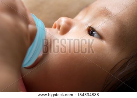Baby girl is sucking milk from bottle before sleep.