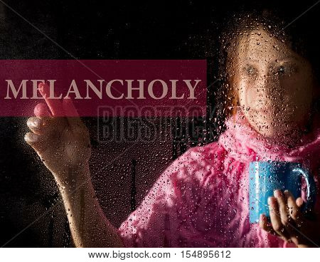 melancholy written on virtual screen. young woman melancholy and sad at the window in the rain, she holding a cup of hot coffee or tea.