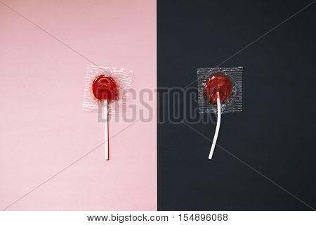 lollipops on pink and black background. the contrast between the whole and broken candy lollipop. the concept of contrast. before and after. top view
