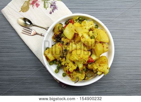Top view of Cauliflower and Potato with green peas Indian dry curry on a plate
