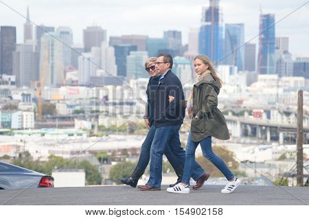 Ordinary family of three - father mother and teenage daughter walking holding hands on the street of big city scyscrapers in the distance.