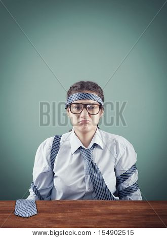 Pouting business woman at the desk with a long necktie wrapped around her