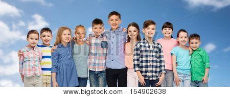 childhood, fashion, friendship and people concept - group of happy smiling children hugging over blue sky and clouds background