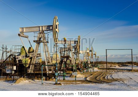 Group of oil pumps and wellheads in the oilfield during winter. Oil and gas concept.