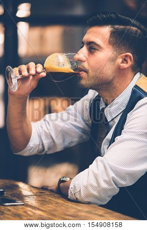 Portrait of handsome man in elegant clothes drinking coffee from wine glass with squinted eyes