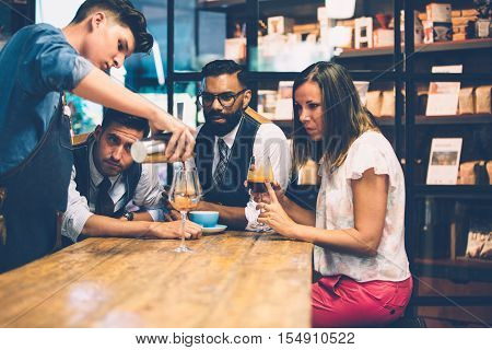 Woman and two men looking at bartender pouring black coffee from shaker in wine glass