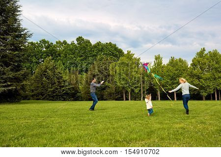 Happy Young Family With Flying A Kite.