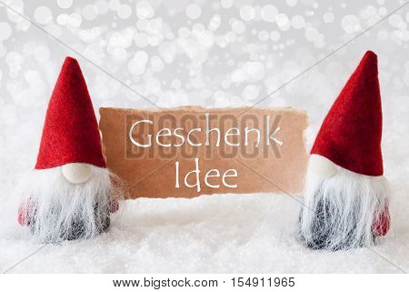 German Text Geschenk Idee Means Gift Idea. Christmas Greeting Card With Two Red Gnomes. Sparkling Bokeh Background With Snow. English Text Seasons Greetings