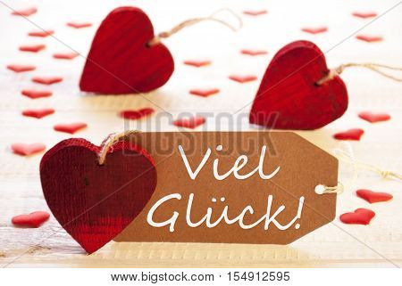 Label With German Text Viel Glueck Means Good Luck. Many Red Heart. Wooden Rustic Or Vintage Background.
