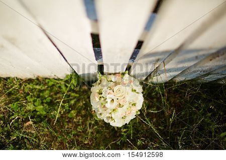 Wedding bouquet on white fense on ceremony place.Top view.