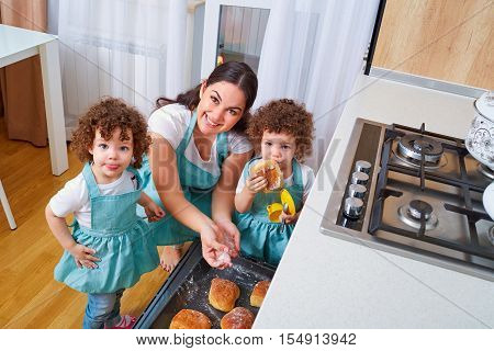 Twins with her mother in the kitchen together preparing meals. Mom with a tray of buns uybaetsya teaches kids to cook twins. Happy family with twins. The concept of a happy family.