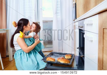 Mom and baby daughter in kitchen hugging and smiling. Mom teaches daughter to cook. Happy family preparing buns. Family playing in the kitchen. Happiness love and care.