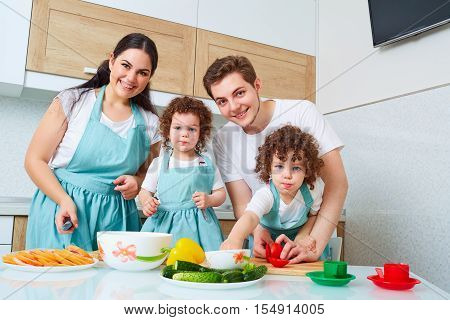 Family Portrait Of Girl Twins And Happy Parents.happy Family With Twin Daughters In The Kitchen. Che