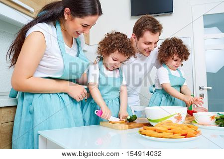 Daughters Twins, Dad And Mom Cook In The Kitchen. A Happy Family. Parents Teach Their Children To Co
