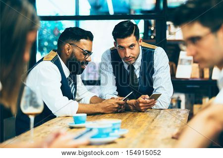 Man in glasses using smartphone while handsome friend looking at camera at table in coffeeshop