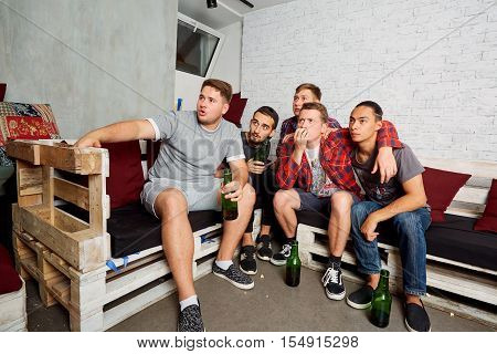 Friends Watching Tv Together Students With Interest And Emotion, Drink Beer, To The Output. Friends