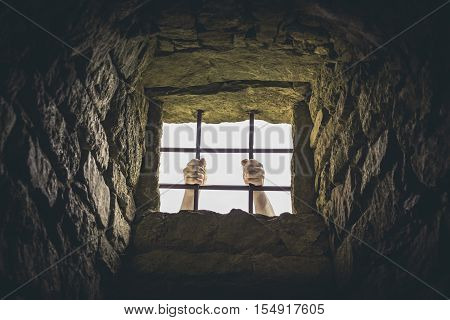 Man grabbing prison bars - Conceptual image with a man's hand grabbing the metal bars from an old medieval prison