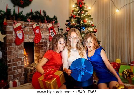 Three beautiful girls friends are opening gifts in the room with the decor Christmas tree fireplace and looking at the magic light of the boxes in Christmas New Year.
