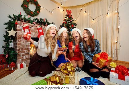 Friends sing karaoke at Christmas New Year. Four beautiful girls in caps of Santa Claus singing with a microphone in the room with the decor.